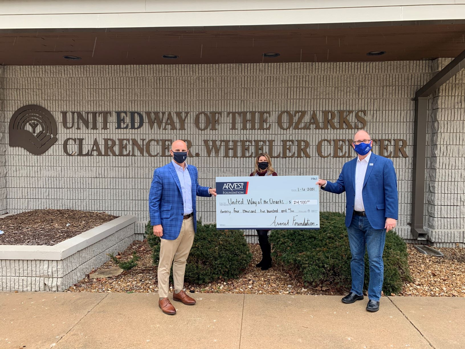 image of Kyle Hubbard, President of Arvest Bank-Springfield, and Pam Yancey, a UWO Board member and Community Market Director, EVP of Arvest Bank, and Greg Burris, President and CEO of United Way of the Ozarks, holding a check in front of the United Way building